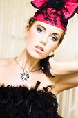 pic of olden days  - dancing show girl performing in front of a stage curtain wearing a black feather blouse pink hat black half gloves and necklace with pendant - JPG