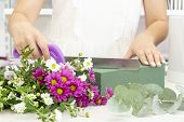 Florist Girl Working In A Flower Shop.girl Florist Cuts Oasis With A Knife. Floristry Business. Flor poster