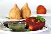 foto of samosa  - Indian deep fried snack cutlet made of potatoes masala and cashew with chutneys and another popular snack samosa in the background - JPG