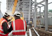 stock photo of excavator  - two foreman discussion on location  construction site - JPG