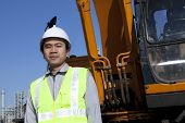picture of heavy equipment operator  - portrait construction worker standing front of heavy equipment - JPG