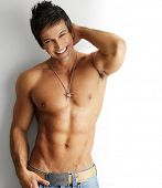 stock photo of hunk  - Sexy smiling shirtless male model flirting against white background - JPG