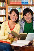 Studenten - junge asiatische Frau und Mann in der Bibliothek mit Laptop und Buch lernen, sie sind eine Grou lernen