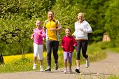 Happy Family with two girls running or jogging for sport and better fitness in a meadow in summer