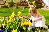 Little Girl on an Easter Egg hunt on a meadow in spring, she has found an Easter egg, the easter bun