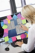 Businesswoman In Office Pointing At Monitor With Notes On