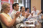 Cinco empresarios en la sala de juntas mesa aplaudiendo y sonriendo