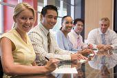 Cinco empresarios sonriendo de la sala de juntas