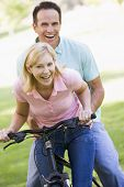 Couples On One Bike Outdoors Smiling