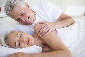 Man Waking Woman Lying In Bed Sleeping