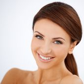 Head and shoulders studio portrait of a smiling happy beautiful woman with a lovely fresh natural complexion isolated on white