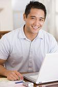 Man In Dining Room Using Laptop Smiling