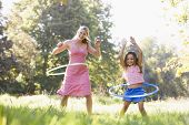 Woman And Young Girl With Hula Hoops Outdoors Smiling