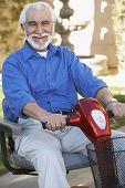 Retrato de un hombre alegre senior en scooter eléctrico