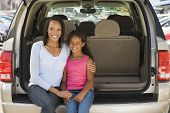 Woman With Young Girl Sitting In Back Of Van Smiling
