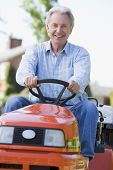 Man Outdoors Driving Lawnmower Smiling