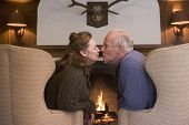Couples Sitting In Living Room By Fireplace Kissing