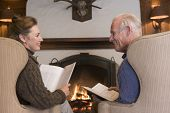 Couples Sitting In Living Room By Fireplace With Books Smiling