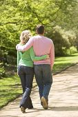 Couples Walking On Path Arm In Arm
