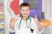 Adorable child with doctor uniform saying Ok in the hospital