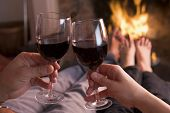 Feet Warming At Fireplace With Hands Holding Wine