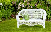 White wicker love seat with watering can in the summer garden.