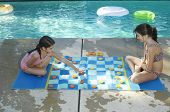 picture of draught-board  - Two girls playing large draughts board beside swimming pool - JPG