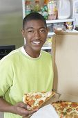 Portrait of young boy holding a slice of pepperoni pizza at home