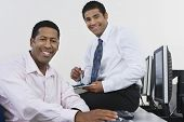 Portrait of happy African American business colleagues sitting at computer desk