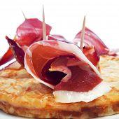 primer plano de una típica tortilla española de patatas y algunos rollos de jamón serrano