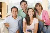 Two Couples Sitting In Living Room Smiling
