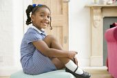 Young Girl In Front Hallway Fixing Shoe And Smiling