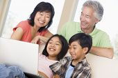 Couples With Two Young Children In Living Room With Laptop Smiling