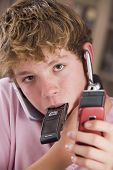 Young Boy In Bedroom Holding Many Cellular Phones
