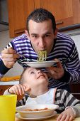 Funny father and little kid eating pasta at kitchen.