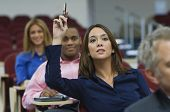 stock photo of middle class  - Female executive raising hand during a business lecture amid colleagues - JPG
