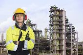 Young chemical engineer posing in front of a biodiesel refinary plant, wearing a hard hat, fire reta