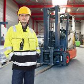 Man, waring safety clothes, including a hard hat, standing proudly in front of his forklift truck in a warehouse