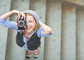 stock photo of stroll  - Happy hipster girl making photo with retro camera on city street - JPG