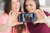 Two happy teenage girls sitting on a sofa taking a photo of themselves with a mobile phone in a livi