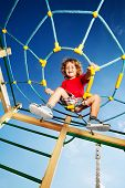 picture of playground  - Happy little three years old child boy climbed on top of the rope web on playground looking down and laughing - JPG