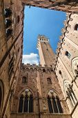 Siena landmark photo. Cortile del Podesta courtyard, Torre del Mangia tower and Palazzo Pubblico building. Bottom view. Tuscany, Italy