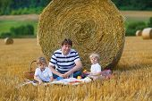 Young Father And Two Little Toddler Boys Picnicking On Yellow Hay Field