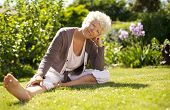 Mature Woman Sitting Down On Grass Comfortably