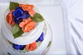 picture of three tier  - Three tier fondant ruffled white wedding cake decorated with orange and purple gum paste roses and green leafs shot from above - JPG