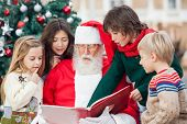 Santa Claus and children reading book against Christmas tree
