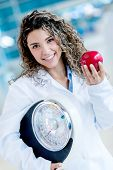 Nutritionist holding a weight scale and an apple - healthy lifestyle