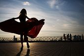Beautiful woman silhouette with a wide hem of dress in the evening at sunset