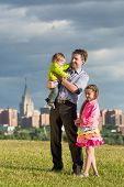 Happy family of three on green grass on a background of city, father holding son in arms.