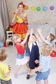 Постер, плакат: Five kids catch soap bubbles which lets entertainer at children party
